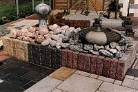 Hier sehen Sie verschiedene Quellsteine eingefasst mit Granitpalisaden