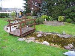 Holzbrücke über den Bachlauf im Garten