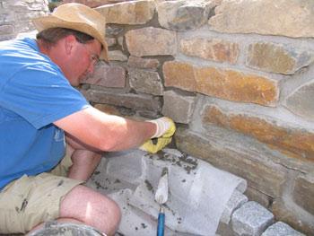 Galabau-Mitarbeiter bei Verfugungsarbeiten an einer Mauer