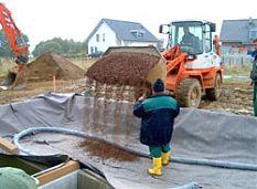 ein Frontlader schüttet Kieselsteine in ein vorbereitetes Teichbett