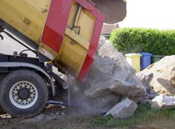 Anlieferung großer Natursteinbrocken mit einem Tieflader