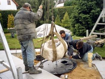 Arbeiter beim Setzen eines Quellsteines