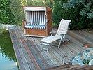 großes Holzdeck mit Strandkorb und Liegestuhl