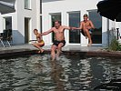 Kinder toben mit Papa im Badeteich