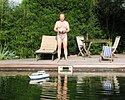 Eigentümer mit funkgesteuertem Modellboot am Schwimmteich