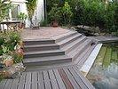 5 Stufen führen von der Holzdeckterrasse zum Schwimmteich