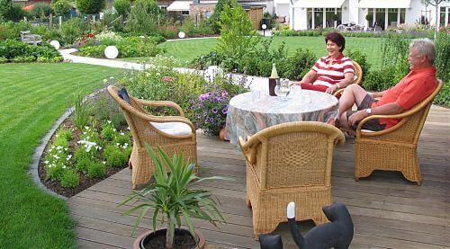 Mann und Frau auf neuer Holzterrasse im landschaftlichen Garten nach der Gartenplanung