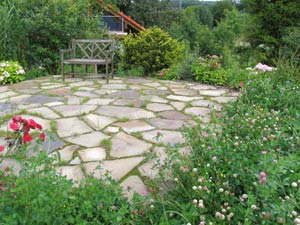 Terrasse mit Polygonalplatten in Blumenwiese